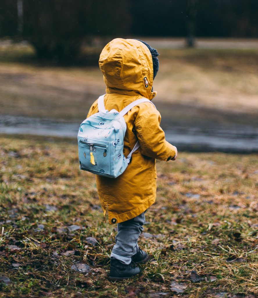 Back of small child wearing a yellow hooded jacket and a light blue backpack walking on grass towards a path