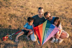 Two fathers holding a rainbow kite with their young children sitting in a field